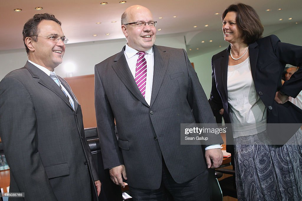 New German Environment Minister Peter Altmaier (C) chats with Interior Minister <a gi-track='captionPersonalityLinkClicked' href=/galleries/search?phrase=Hans-Peter+Friedrich&family=editorial&specificpeople=7528072 ng-click='$event.stopPropagation()'>Hans-Peter Friedrich</a> and Agriculture and Consumer Protection Minister <a gi-track='captionPersonalityLinkClicked' href=/galleries/search?phrase=Ilse+Aigner&family=editorial&specificpeople=2158567 ng-click='$event.stopPropagation()'>Ilse Aigner</a> upon Altmaier's arrival for his first German government weekly cabinet meeting since his appointment on May 23, 2012 in Berlin, Germany. Altmaier, who succeeds Norbert Roettgen, will have the formidable task of helping German Chancellor Angela Merkel execute her transfer of Germany towards renewable energy sources.