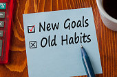 New Goals Old Habits written in note with pen, calculator and cup of coffee on wooden desk. Business concept. Top view.