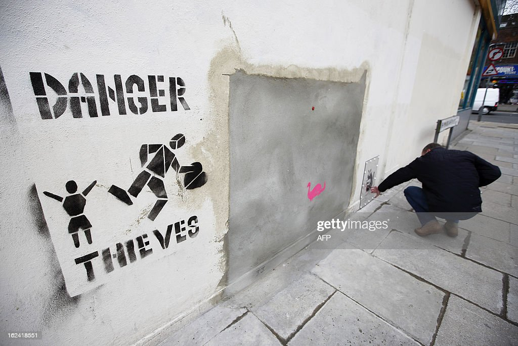 New graffiti work that reads 'Danger Thieves' is placed next to a section of a wall where celebrated street artist Banksy's 'Slave Labour' graffiti artwork was removed in north London on February 23, 2013. The work that showed a young boy using a sewing machine to make the British flag has been carefully removed and will be auctioned in Miami where it's expected to fetch around 328,000 GBP (500,000 USD). Residents of the North London area have reacted angrily to the removal of the work, but the auction house says the piece was acquired legally.