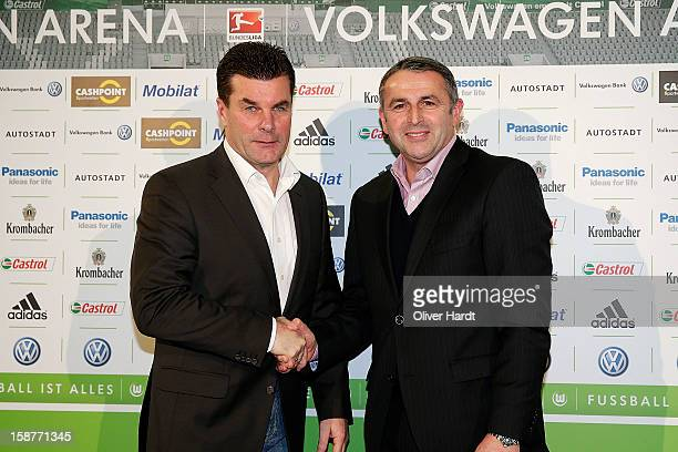 New head coach Dieter Hecking of Vfl Wolfsburg shakes hands with Sporting director Klaus Allofs during a press conference at Volkswagen Arena on...