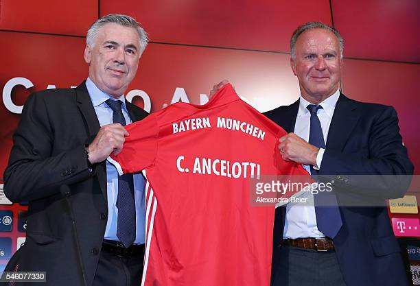New head coach of FC Bayern Muenchen Carlo Ancelotti receives a FC Bayern Muenchen jersey by CEO KarlHeinz Rummenigge after Ancelotti's first press...