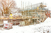 Construction site building a new brick home during winter time, snowing conditions