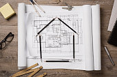 Top view of architectural blueprints, rolls and drawing instruments on the worktable. Shape of house with black pencils on a project house. Architectural drawings with house keys on wooden table, new