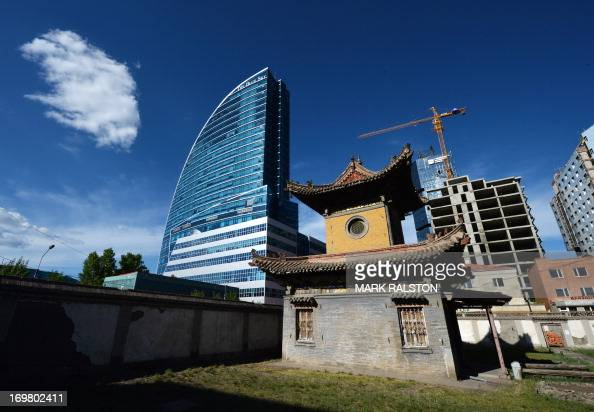 A new hotel and office building stands beside the ancient Choijin Temple in Ulan Bator Mongolia on June 2 2013 The country is in the middle of a...