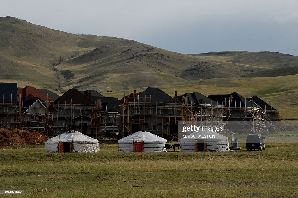 New housing under construction is pictured behind traditional Mongolian tents called a 'ger' or 'yurt' outside Ulan Bator on June 4, 2013. The country is in the middle of a resources boom with the huge copper and gold Oyu Tolgoi soon to open and which will provide vast revenues for the government that can be spent on infrastructure and education if corruption can be kept in check. AFP PHOTO / Mark RALSTON
