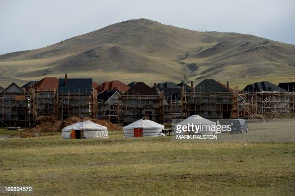 New housing under construction is pictured behind traditional Mongolian tents called a 'ger' or 'yurt' outside Ulan Bator on June 4 2013 The country...
