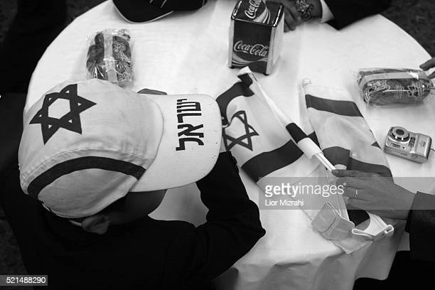 A new immigrant boy from the 'Bnei Menashe' tribe gets an Israeli flag after arrives in Ben Gurion International Airport in Lod as they emigrate from...