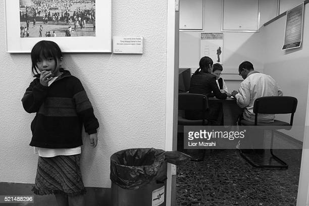 A new immigrant girl from the 'Bnei Menashe' tribe waits to Israeli officials after arrives in Ben Gurion International Airport in Lod as they...
