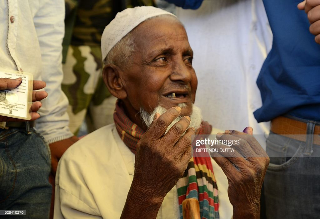 New Indian citizen of Masaladanga enclave 103 year old Asgar Ali(C) is helped by his grandson Jamal Ali after casting his vote at a polling station in Cooch Behar district on May 5, 2016, during the final phase of state assembly elections in the eastern Indian state of West Bengal. Ali is among many who became Indian citizens after a transfer of enclaves between India and Bangladesh in 2015, when India and Bangladesh signed a Land Boundary Agreement. Under the agreement Bangladesh had transferred 51 enclaves to India while India transferred 111 to Bangladesh. / AFP / DIPTENDU