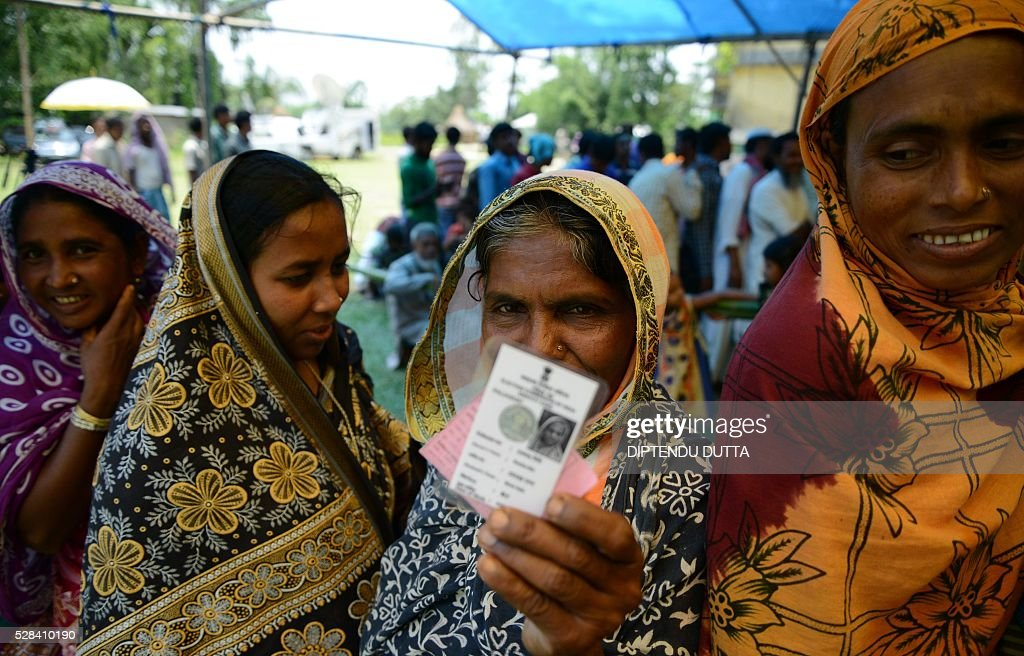 New Indian citizen of Masaladanga enclaves Shelaha Bibi 69,holds her voter identity card as she waits with others to casting their ballots at a polling station in Cooch Behar district on May 5, 2016,during the final phase of state assembly elections in the eastern Indian state of West Bengal. Bibi is among many who became Indian citizens after a transfer of enclaves between India and Bangladesh in 2015, when India and Bangladesh signed a Land Boundary Agreement. Under the agreement Bangladesh had transferred 51 enclaves to India while India transferred 111 to Bangladesh. / AFP / DIPTENDU