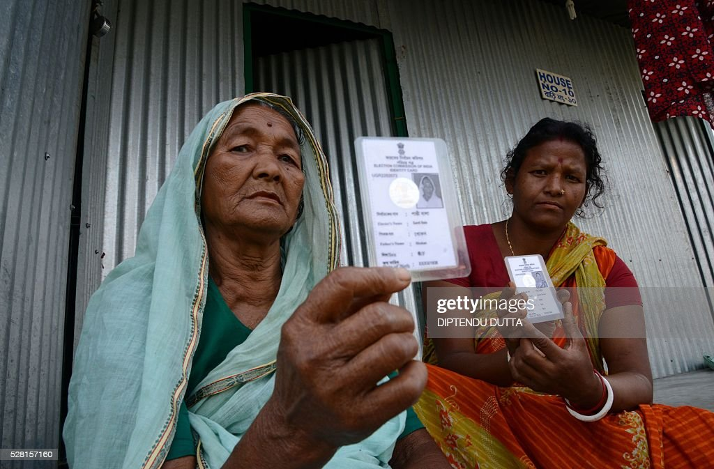 New Indian citizen Santi Bala(L)poses with her new voter identity card at Dinhata Enclave settlement camp in Cooch Behar district on May 4, 2016, on the eve of voting in the final phase of state assembly elections in the eastern Indian state of West Bengal. Santi is among many who became Indian citizens after a transfer of enclaves between India and Bangladesh in 2015, when India and Bangladesh signed a Land Boundary Agreement. Under the agreement Bangladesh had transferred 51 enclaves to India while India transferred 111 to Bangladesh. / AFP / DIPTENDU