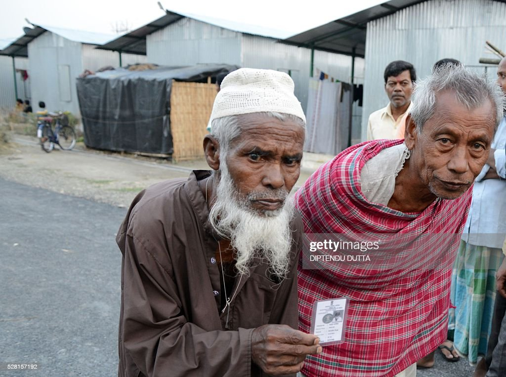 New Indian citizens Dhirendranath Barman(R)and Abibul Aziz(L) hold their voter identity cards at Dinhata Enclave settlement camp in Cooch Behar district on May 4, 2016, on the eve of voting in the final phase of state assembly elections in the eastern Indian state of West Bengal. The elderly pair are among many who became Indian citizens after a transfer of enclaves between India and Bangladesh in 2015, when India and Bangladesh signed a Land Boundary Agreement. Under the agreement Bangladesh had transferred 51 enclaves to India while India transferred 111 to Bangladesh. / AFP / DIPTENDU