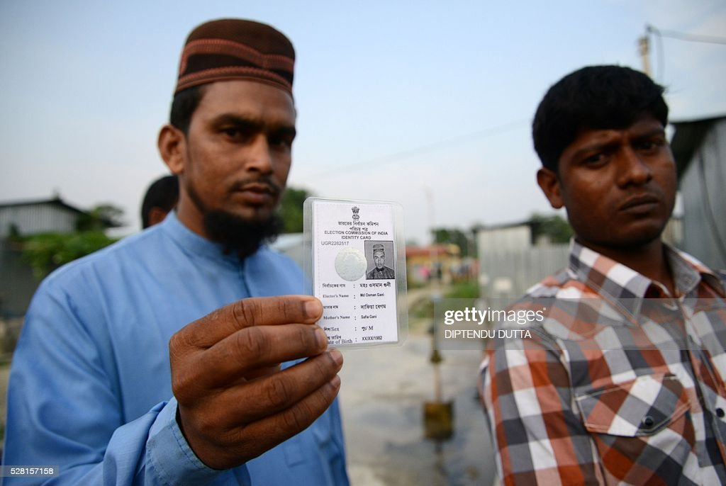 New Indian citizens Md. Osman Gani(L)and Mofiz pose with their new voter identity cards at Dinhata Enclave settlement camp in Cooch Behar district on May 4, 2016, on the eve of voting in the final phase of state assembly elections in the eastern Indian state of West Bengal. The men are among many who became Indian citizens after a transfer of enclaves between India and Bangladesh in 2015, when India and Bangladesh signed a Land Boundary Agreement. Under the agreement Bangladesh had transferred 51 enclaves to India while India transferred 111 to Bangladesh. / AFP / DIPTENDU