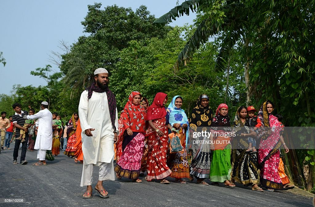 New Indian citizens of Masaladanga and nearby enclaves arrive to cast their ballots at a polling station in Cooch Behar district on May 5, 2016, during the final phase of state assembly elections in the eastern Indian state of West Bengal. The pair were among many who became Indian citizens after a transfer of enclaves between India and Bangladesh in 2015, when India and Bangladesh signed a Land Boundary Agreement. Under the agreement Bangladesh had transferred 51 enclaves to India while India transferred 111 to Bangladesh / AFP / DIPTENDU