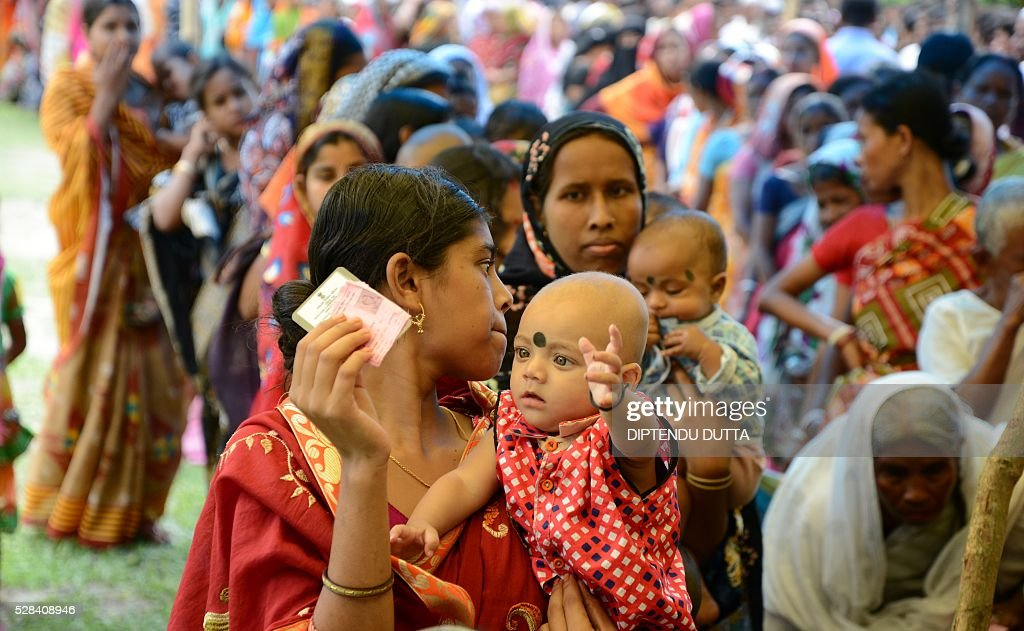 New Indian citizens of Masaladanga and nearby enclaves queue to cast their ballots at a polling station in Cooch Behar district on May 5, 2016, during the final phase of state assembly elections in the eastern Indian state of West Bengal. The pair were among many who became Indian citizens after a transfer of enclaves between India and Bangladesh in 2015, when India and Bangladesh signed a Land Boundary Agreement. Under the agreement Bangladesh had transferred 51 enclaves to India while India transferred 111 to Bangladesh / AFP / DIPTENDU