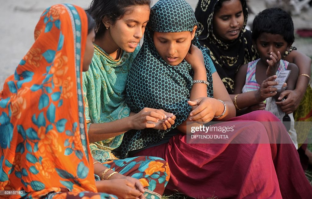 New Indian citizens Parul(L)and Hafiza(C)examine their new voter identity cards at Dinhata Enclave settlement camp in Cooch Behar district on May 4, 2016, on the eve of voting in the final phase of state assembly elections in the eastern Indian state of West Bengal. The pair were among many who became Indian citizens after a transfer of enclaves between India and Bangladesh in 2015, when India and Bangladesh signed a Land Boundary Agreement. Under the agreement Bangladesh had transferred 51 enclaves to India while India transferred 111 to Bangladesh. / AFP / DIPTENDU
