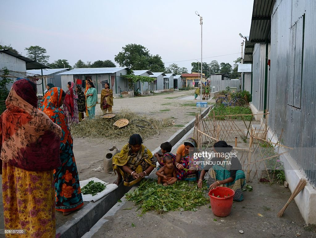 New Indian citizens prepare vegetables in an open space at Dinhata Enclave settlement camp in Cooch Behar district on May 4, 2016, on the eve of voting in the final phase of state assembly elections in the eastern Indian state of West Bengal. The women are among many who became Indian citizens after a transfer of enclaves between India and Bangladesh in 2015, when India and Bangladesh signed a Land Boundary Agreement. Under the agreement Bangladesh had transferred 51 enclaves to India while India transferred 111 to Bangladesh. / AFP / DIPTENDU