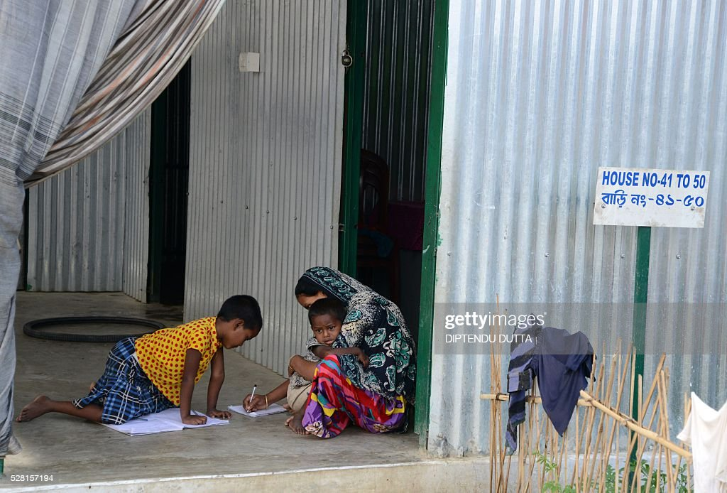 New Indian citizens study with the help of their mother at Dinhata Enclave settlement camp in Cooch Behar district on May 4, 2016, on the eve of voting in the final phase of state assembly elections in the eastern Indian state of West Bengal. The family are among many who became Indian citizens after a transfer of enclaves between India and Bangladesh in 2015, when India and Bangladesh signed a Land Boundary Agreement. Under the agreement Bangladesh had transferred 51 enclaves to India while India transferred 111 to Bangladesh. / AFP / DIPTENDU