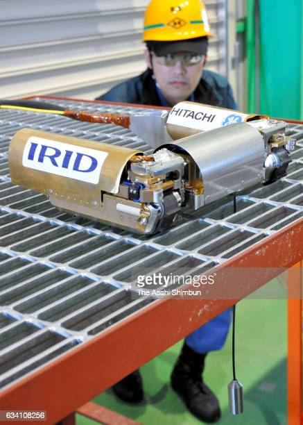 A new investigative robot equipped with a censoring unit hanging through metal grating is demonstrated on February 3 2017 in Hitachi Ibaraki Japan...