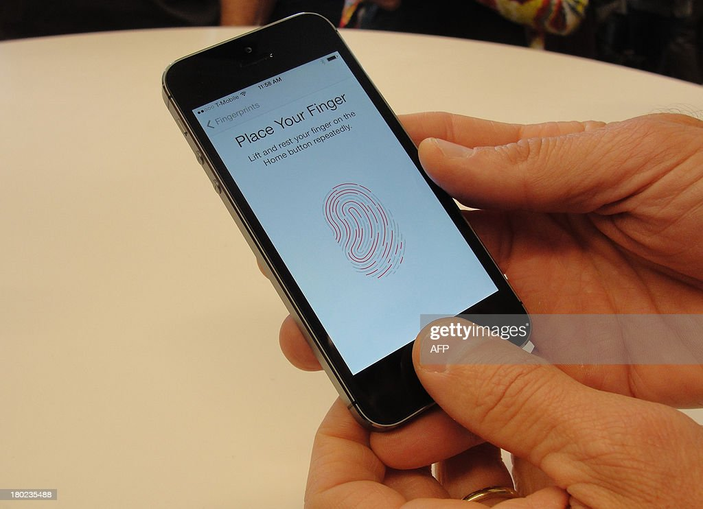 New iPhone 5S handsets let people use their fingerprints to unlock the smartphones at an iPhone event at Apple's headquarters in Silicon Valley on September 10, 2013 in Cupertino, California. Apple unveiled two new iPhones on Tuesday in its bid to expand its share of the smartphone market, including one as low as $99 with a US carrier contract. 'The business has become so large that this year we are going to replace the iPhone 5 and we are going to replace it with two new designs,' Apple chief Tim Cook announced at the company's Silicon Valley headquarters. Apple will begin taking orders on Friday, and on September 20 the two devices will go on sale in the United States, Australia, Britain, China, France, Germany, Japan and Singapore. AFP PHOTO/GLENN CHAPMAN