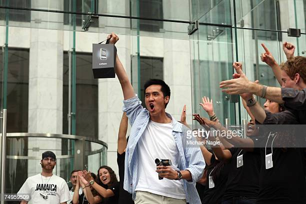 New iPhone owners exit Apple's flagship store and show their iPhones off to the media on Fifth Avenue on June 29 2007 in New York City Hype for the...