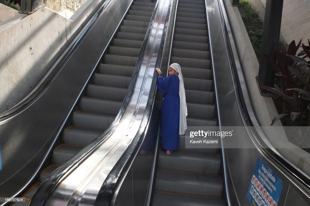 A New Israelites girl wearing Old Testament costumes uses the escalators in '20 de Julio' neighborhood in the Comuna 13 slums on January 5, 2013 in Medellin, Colombia. The stairway is divided into six sections and has a length of 1,260 feet. An escalator goes up and a second goes down.Residents used to climb hundreds of steps to get home from the bottom of the hill, but the journey now takes just 6 minutes. Comuna 13 is the most notorious slums of Medellin with violence occurring everyday.