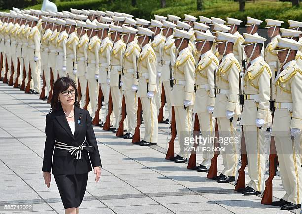 New Japanese Defence Minister Tomomi Inada reviews an honour guard during a welcoming ceremony at the Defence Ministry in Tokyo on August 4 2016...