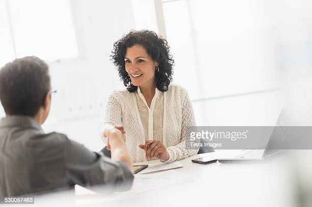 USA, New Jersey, Business people shaking hands at desk in office