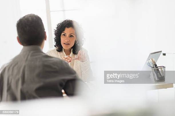 USA, New Jersey, Business people talking at desk in office