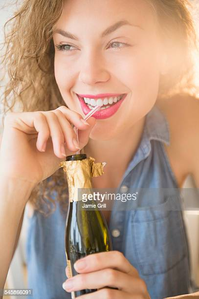 USA, New Jersey, Cheerful young woman sipping champagne from bottle