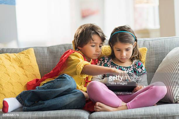 USA, New Jersey, Children (6-7) playing game on tablet pc at home