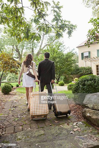 USA, New Jersey, Couple walking up path with luggage