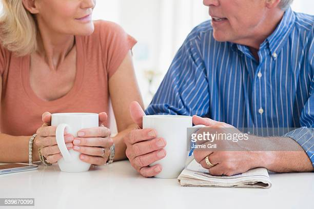 USA, New Jersey, Cropped shot of husband and wife drinking coffee and talking