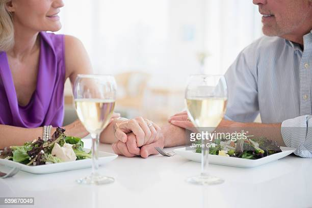 USA, New Jersey, Cropped view of couple holding hands in restaurant with glasses of white wine in foreground
