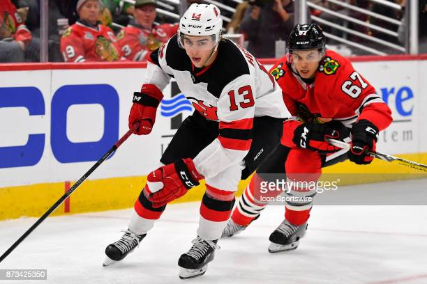 New Jersey Devils center Nico Hischier advance with the puck while pursed by Chicago Blackhawks center Tanner Kero during the game between the New...