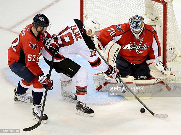 New Jersey Devils center Travis Zajac just misses a pass in front of Washington Capitals goalie Braden Holtby and Capitals defenseman Mike Green in...