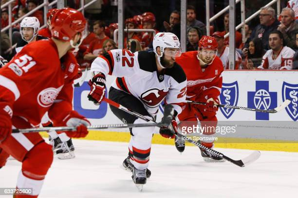 New Jersey Devils defenseman Kyle Quincey and Detroit Red Wings forward Darren Helm chase after the puck during a regular season NHL hockey game...