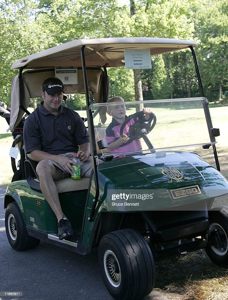 New Jersey Devils forward John Madden is driven around the course by son John Tyler during the New Jersey Devils Alumni Golf Tournament on August 21...