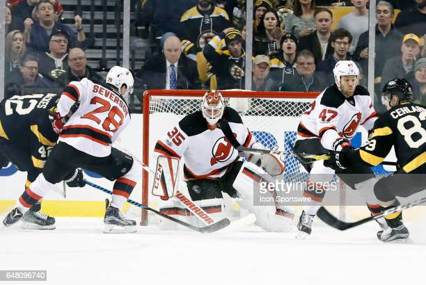 New Jersey Devils goalie Cory Schneider keeps his eyes on the puck as c28 handles Boston Bruins center David Backes and New Jersey Devils defenseman...