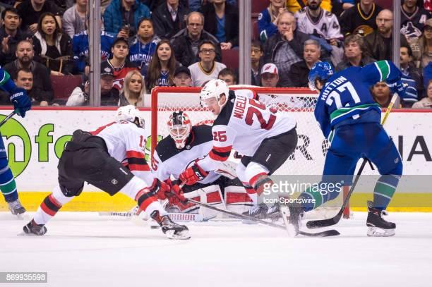 New Jersey Devils Goalie Cory Schneider tracks the puck as New Jersey Devils Center Nico Hischier and New Jersey Devils Defenceman Mirco Mueller...