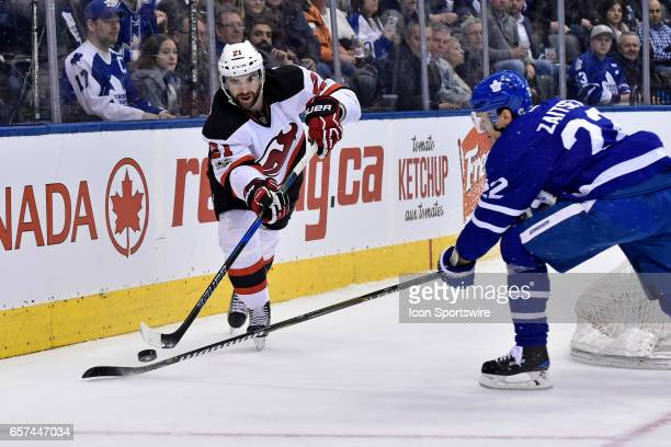 New Jersey Devils Right Wing Kyle Palmieri passes the puck past Toronto Maple Leafs Defenceman Nikita Zaitsev during the regular season NHL game...
