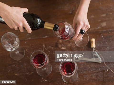 USA, New Jersey, Elevated view of woman pouring red wine