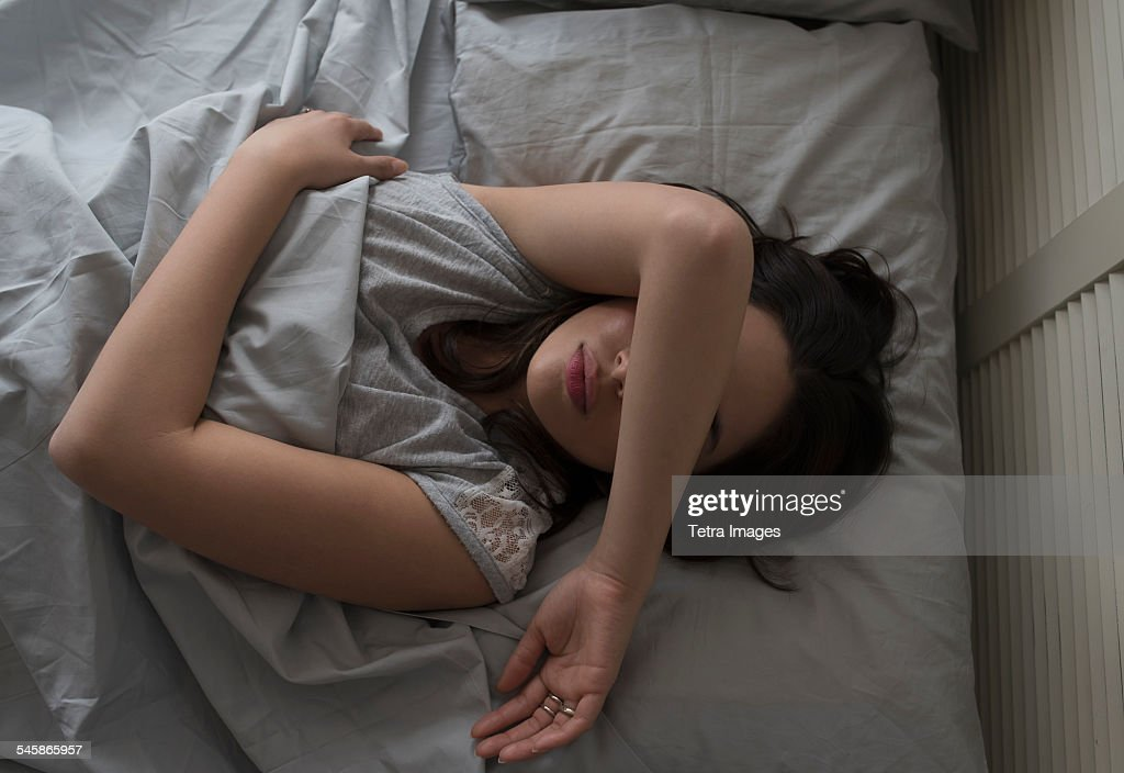USA, New Jersey, Elevated view of young woman sleeping in bed