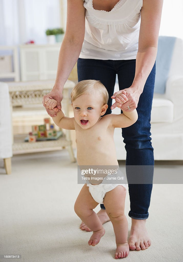 USA, New Jersey, Jersey City, Baby boy (6-11 months) walking with mother