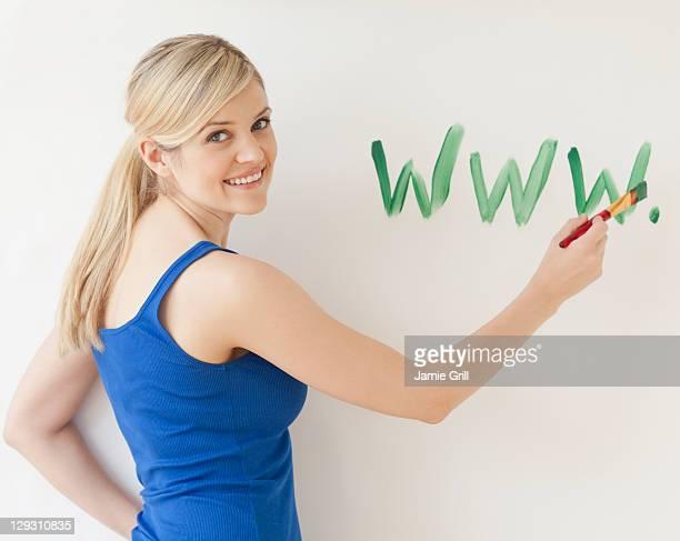 USA, New Jersey, Jersey City, Blonde young woman writing web address on wall