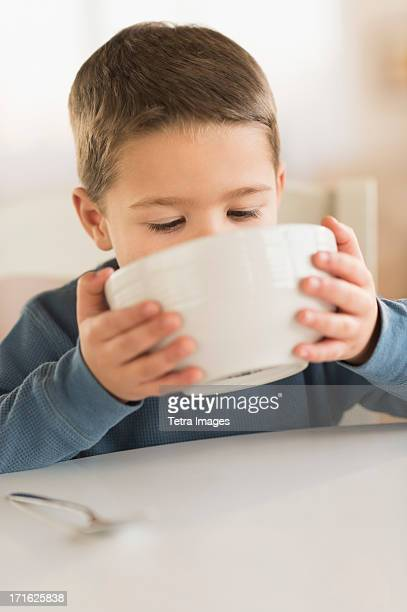 USA, New Jersey, Jersey City, Boy (4-5) drinking from bowl