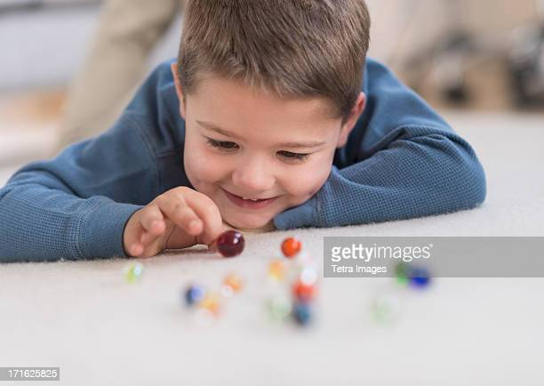 USA, New Jersey, Jersey City, Boy (4-5) playing with marbles