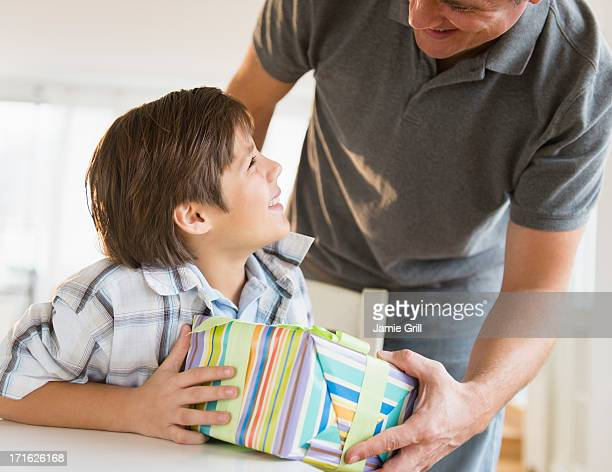 USA, New Jersey, Jersey City, Boy (8-9) receiving gift from father