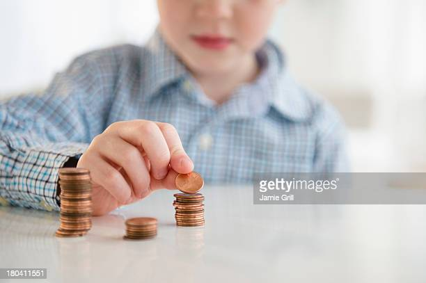 USA, New Jersey, Jersey City, Boy (4-5) stacking coins