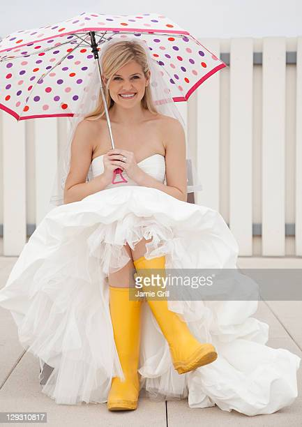 USA, New Jersey, Jersey City, Bride sitting in yellow rubber boots with umbrella